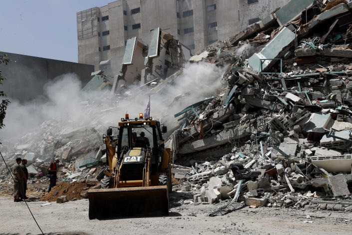 Workers clear the rubble of a building that was destroyed by an Israeli airstrike on Saturday that housed The Associated Press, broadcaster Al-Jazeera and other media outlets, in Gaza City, Sunday, May 16, 2021. (AP Photo/Adel Hana)