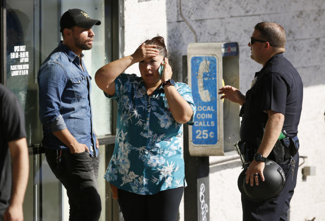 <p>An unidentified Trader Joe's supermarket employee, center, talks on her phone as Los Angeles Police evacuate a group of witnesses. (Photo: Damian Dovarganes/AP) </p>