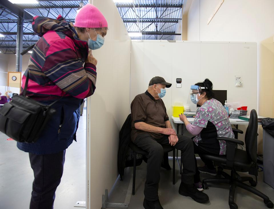 Helene Jolicoeur watches as her 88 year old husband Robert Proteau gets vaccinated against the coronavirus disease (COVID-19) in a clinic in Laval, Quebec, Canada February 25, 2021. REUTERS/Christinne Muschi