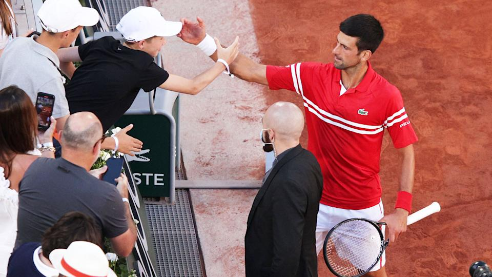 Novak Djokovic, pictured here celebrating with the young fan after winning the French Open.