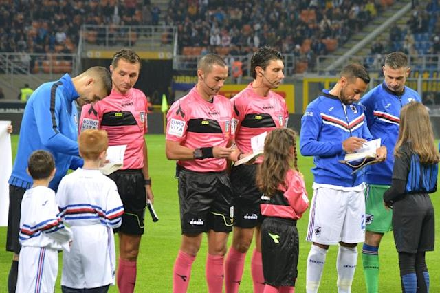 "Inter Milan captain Mauro Icardi (L), Sampdoria counterpart Fabio Quagliarella (2ndR) and referee Marco Guida (C) sign copies of ""The Diary of Anne Frank"" and Primo Levi's memoir ""If This Is A Man"" to child mascots accompanying players onto the pitch (AFP Photo/Paolo RATTINI)"