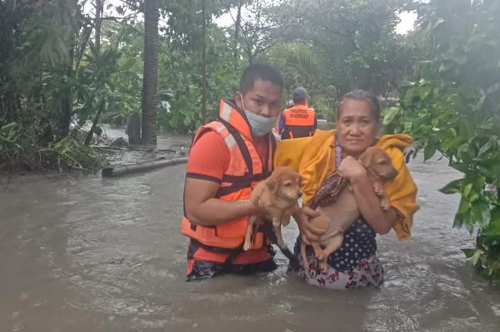 In this handout photo provided by the Philippine Coast Guard, a rescuer helps a woman carry her puppies along floodwaters caused by tropical storm Conson in Naic, Cavite province, Philippines on Wednesday Sept. 8, 2021. Typhoon Conson on Tuesday slammed into the eastern Philippines, causing power outages, suspension of work in government offices, and flooding in some areas. The weather bureau later downgraded it to a tropical storm. (Philippine Coast Guard via AP)