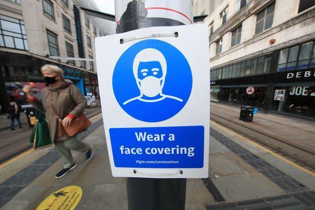 A sign advising on wearing face coverings at a tram stop in Manchester