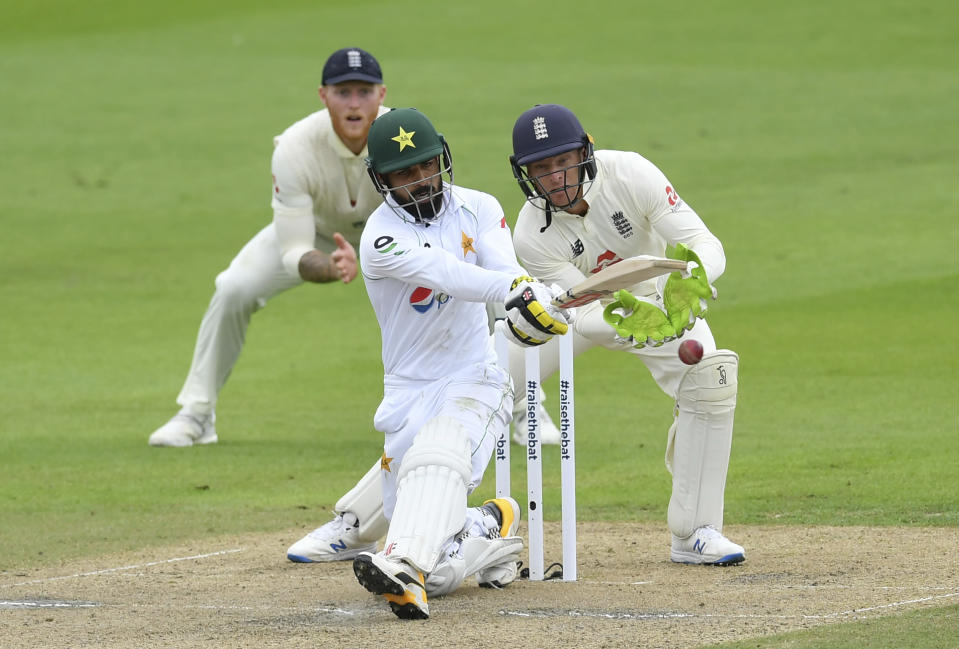 Pakistan's Shadab Khan, center, plays a shot during the second day of the first cricket Test match between England and Pakistan at Old Trafford in Manchester, England, Thursday, Aug. 6, 2020. (Dan Mullan/Pool via AP)