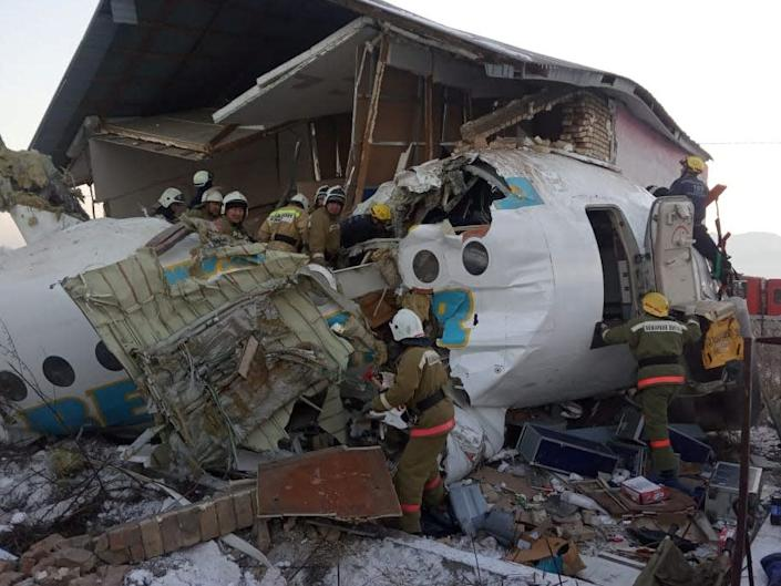 Emergency and security personnel are seen at the site of a plane crash near Almaty, Kazakhstan, December 27, 2019.