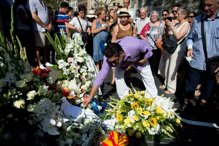 A man lays flowers in memory of the victims of last year's terror attack in Barcelona