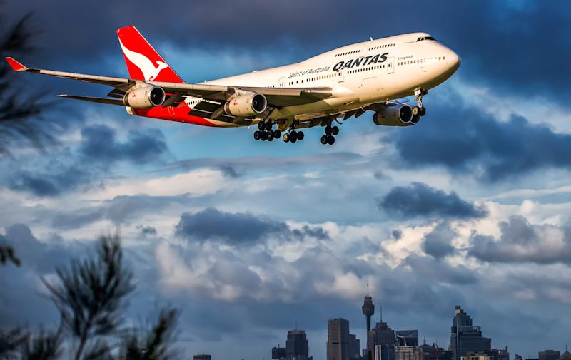 Sydney Australia March 15, 2016, Boeing 747-400 wearing Qantas Airlines colour scheme, arriving late afternoon at Kingsford Smith airport from Bangkok Thailand, with the city Skyline in the background