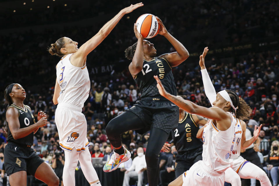Las Vegas Aces guard Chelsea Gray (12) shoots between Phoenix Mercury guards Diana Taurasi (3) and Shey Peddy (5) during the second half of Game 5 of a WNBA basketball playoff series Friday, Oct. 8, 2021, in Las Vegas. (AP Photo/Chase Stevens)