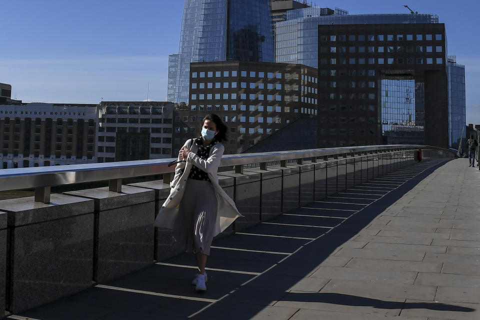 A woman wearing a face mask to protect against coronvirus, walks over London Bridge in London, Tuesday, May 12, 2020. Britain's Prime Minister Boris Johnson announced Sunday that people could return to work if they could not work from home. (AP Photo/Alberto Pezzali)