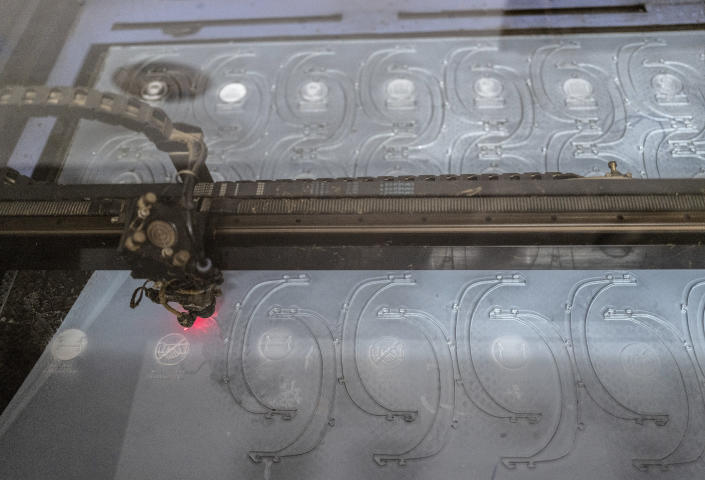In this photo taken Thursday, April 16, 2020, a laser cutter makes protective face shields, to be used to protect against transmission of the coronavirus, at the FabLab workshop at the Ker Thiossane multimedia center in Dakar, Senegal. Researchers across Africa are looking for ways to make their own ventilators, protective equipment and hand sanitizers as the continent faces a peak in coronavirus cases long after the United States and European countries have bought up global supplies during the pandemic. (AP Photo/Sylvain Cherkaoui)