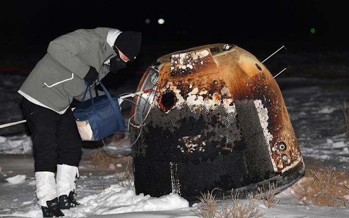 A researcher works next to Chang'e-5 lunar return capsule - Reuters