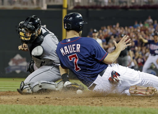 Minnesota Twins' Joe Mauer, right, beats the tag attempt by Chicago White Sox catcher Josh Phegley to score the tying run in the eighth inning of a baseball game on an RBI single by Justin Morneau, Thursday, Aug. 15, 2013, in Minneapolis. The Twins won 4-3. (AP Photo/Jim Mone)