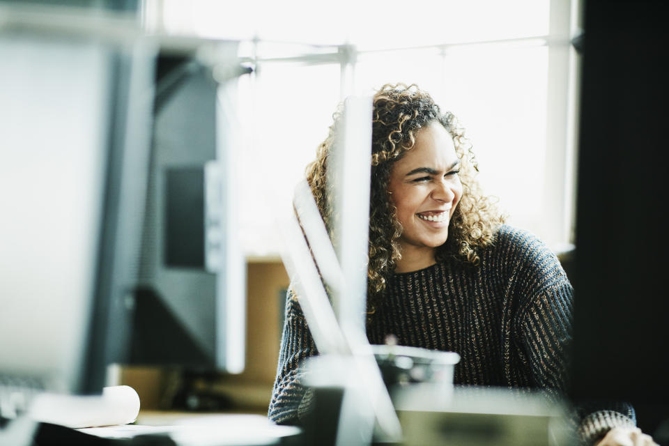 Laughing businesswoman working at workstation in office