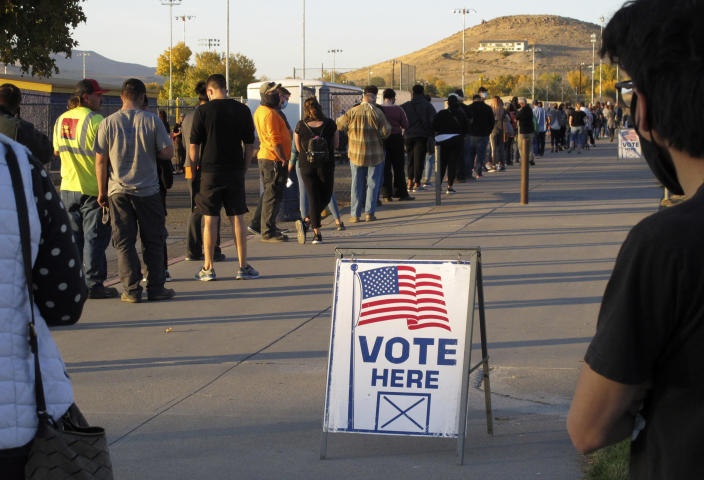 FILE - In this Nov. 3, 2020, file photo, mostly masked northern Nevadans wait to vote in-person at Reed High School in Sparks, Nev., prior to polls closing. U.S. officials say they found no evidence that foreign actors changed votes or otherwise disrupted the voting process in last November's presidential election. That's according to government reports on March 16, 2021, affirming the integrity of the contest won by President Joe Biden. (AP Photo/Scott Sonner, File)