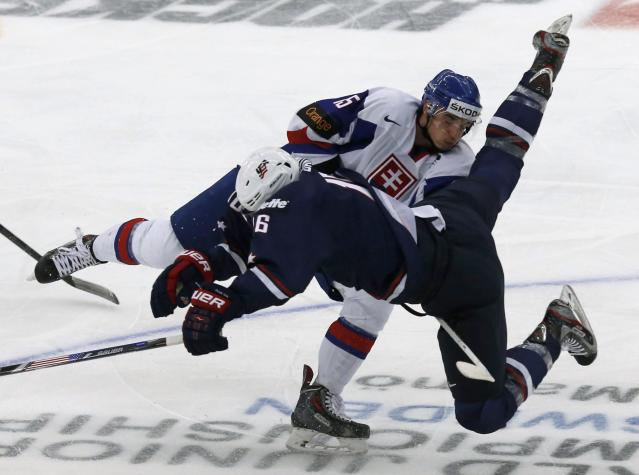 Slovakia's Mario Lunter (L) checks Steven Santini of the U.S during the first period of their IIHF World Junior Championship ice hockey game in Malmo December 28, 2013. REUTERS/Alexander Demianchuk (SWEDEN - Tags: SPORT ICE HOCKEY)