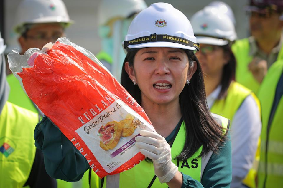Malaysia's Minister of Energy, Science, Technology, Environment and Climate Change Yeo Bee Yin shows a sample of plastic waste shipment in Port Klang, Malaysia, Tuesday, May 28, 2019. Malaysia says it will send back some 3,000 metric tonnes (330 tons) of non-recyclable plastic waste to countries including the U.S., U.K., Canada and Australia in a move to avoid becoming a dumping ground for rich nations. (AP Photo/Vincent Thian)