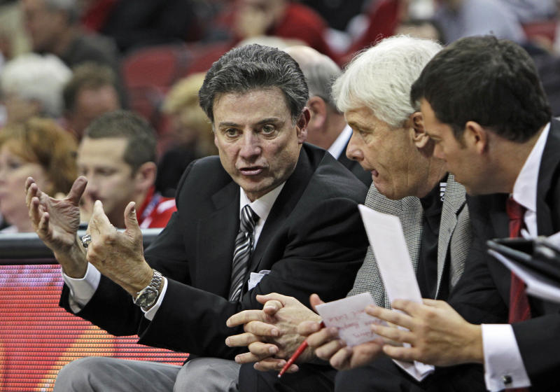 Louisville coach Rick Pitino, left, gestures as he talks with assistants Ralph Willard, center, and Steve Masiello, right, on the bench during an NCAA college basketball exhibition game against Northern Kentucky in Louisville, Ky., Sunday, Oct. 31, 2010. Louisville beat Northern Kentucky 83-66. (AP Photo/Garry Jones)