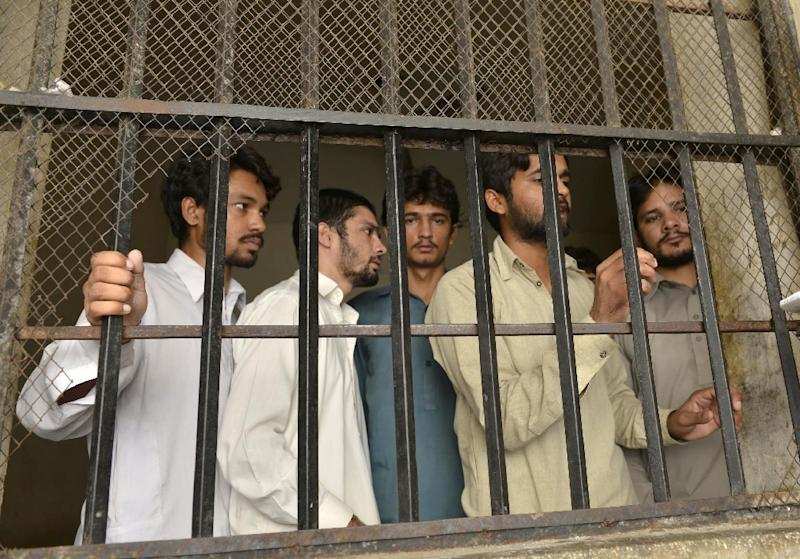 Arrested gang members of a sexual abuse scandal stand in the police lockup in Hussain Khanwala village, some 55 kms southwest of Lahore on August 9, 2015 (AFP Photo/Arif Ali)