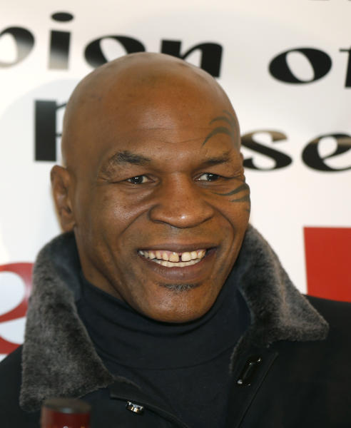 FILE - In this Saturday, Feb. 16, 2013 file photo, former heavyweight champion Mike Tyson smiles during a promotional event for former five-time champion Evander Holyfield's Real Deal barbecue sauce at a Chicago grocery store. Tyson and his wife sued SFX Financial Advisory Management Services, a subsidiary of Live Nation Entertainment on Wednesday Feb. 20, 2013, claiming a former employee of the financial services company embezzled more than $300,000 from them and cost them millions in lucrative contracts. (AP Photo/Charlie Arbogast)