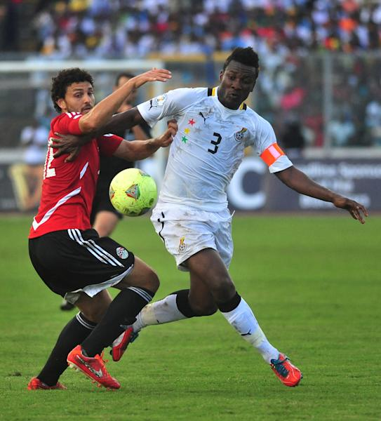 Ghana captain Asamoah Gyan, right, is challenged by Egypt's Hossam Ghaly during their World Cup playoff soccer match in Kumasi, Ghana, Tuesday, Oct. 15, 2013. Ghana stunned Egypt 6-1 in the first leg of their World Cup playoff on Tuesday, with Gyan's fifth-minute goal kicking off a dominant performance that makes the Black Stars overwhelming favorites to be one of the five African teams in Brazil next year. (AP Photo)