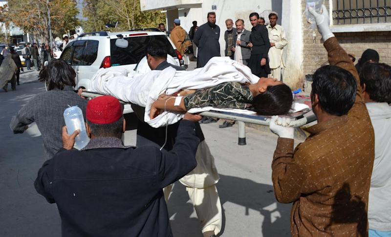 Pakistani volunteers carry an injured polio female health worker to a hospital in Quetta, on November 26, 2014