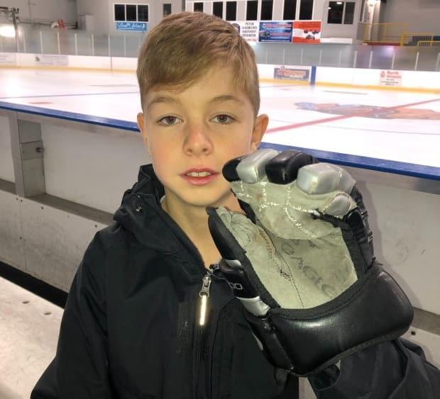 Carter Burton, 11, is now able to play minor hockey thanks to a creative engineer who designed a hockey glove specifically for his left hand.  (Colleen Connors/CBC - image credit)