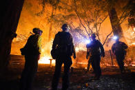 Firefighters make a stand in the backyard of a home in front of the advancing CZU August Lightning Complex Fire Friday, Aug. 21, 2020, in Boulder Creek, Calif. (AP Photo/Marcio Jose Sanchez)