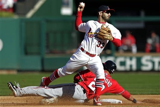 St. Louis Cardinals second baseman Daniel Descalso (33) throws to first but cannot complete the double play after forcing Washington Nationals' Ian Desmond out at second during the fourth inning of Game 1 of the National League division baseball series, Sunday, Oct. 7, 2012, in St. Louis. (AP Photo/Charlie Riedel)