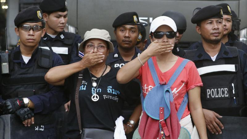 People cover their mouths in front of riot police during a rally at the Victory Monument in Bangkok