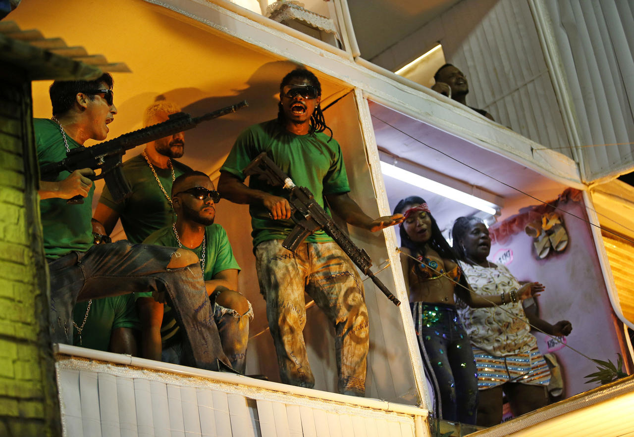 <p>Members from the Beija Flor samba school perform as drug traffickers during Carnival celebrations at the Sambadrome in Rio de Janeiro, Brazil, early Tuesday, Feb. 13, 2018. Brazil's most famous city has long struggled with violence, particularly in the hundreds of slums controlled by drug traffickers, plus criminal assaults and increasing shootouts between drug traffickers and police. (Photo: Silvia Izquierdo/AP) </p>