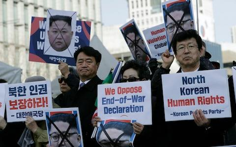 South Korean protesters and North Korean defectors hold portraits of North Korean leader Kim Jong-un during a rally urging the United States to discuss North Korean human rights issues - Credit: AP
