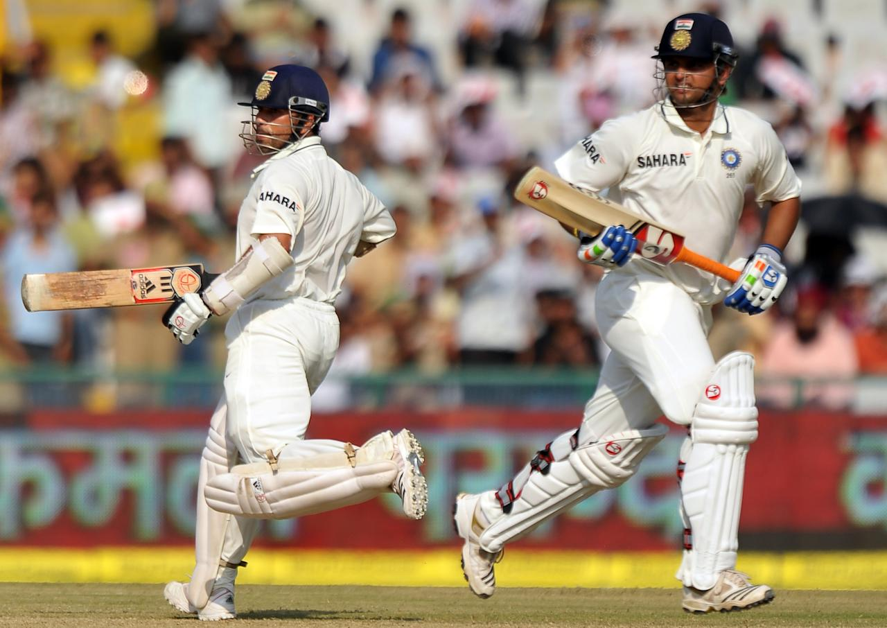 Indian cricketer Sachin Tendulkar (L) and Suresh Raina complete a run during the third day of the opening Test between India and Australia in Mohali on October 3, 2010. In reply to Australia's first innings score of  428 runs, India scored 405 in their first innings.   AFP PHOTO/Dibyangshu SARKAR (Photo credit should read DIBYANGSHU SARKAR/AFP/Getty Images)