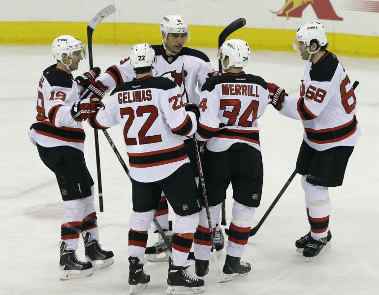 New Jersey Devils' Travis Zajac (19), Eric Gelinas (22), Jon Merrill (34) and Jaromir Jagr (68), of the Czech Republic, celebrate with Dainius Zubrus, facing camera, of Lithuania, following Zubrus' goal against the Carolina Hurricanes during the third period of an NHL hockey game in Raleigh, N.C., Friday, Nov. 29, 2013. New Jersey won 5-2. (AP Photo/Gerry Broome)