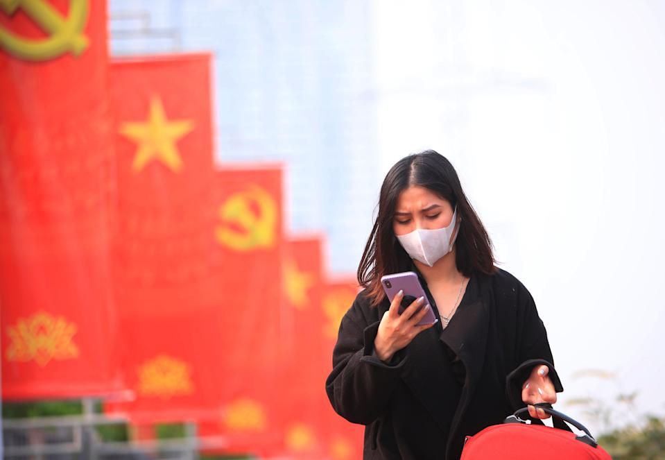 <p>A woman in a face mask in Vietnam</p> (AP)