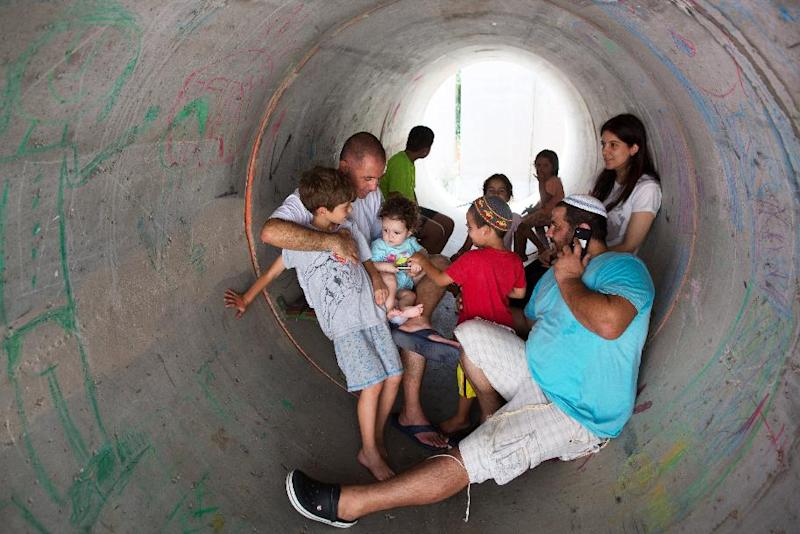 Israelis hide in a large concrete pipe used as a shelter during a Palestinian rocket attack on the southern Israeli village of Nitzan on July 10, 2014 (AFP Photo/Menahem Kahana)