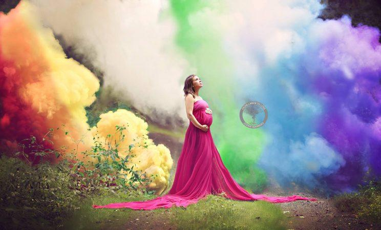 Pregnant woman stands in reverie against a background of rainbow colored smoke