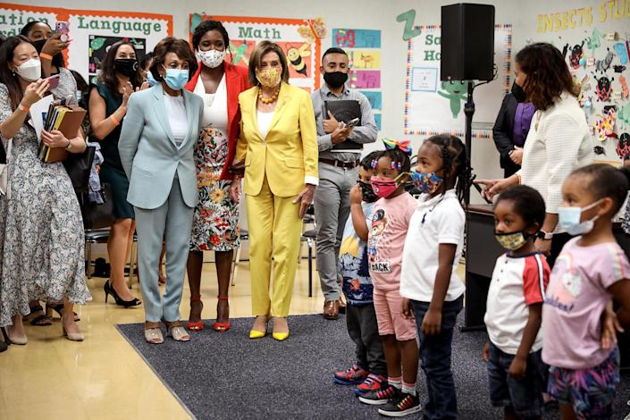 Rep. Maxine Waters, D-Calif., left, Ifetayo Ewing, director of Ethel Bradley Early Education Center, and House Speaker Nancy Pelosi are greeted by students before a news conference to discuss the importance of the Child Tax Credit at the Ethel Bradley Ear (Gary Coronado / Los Angeles Times via Getty Images file)