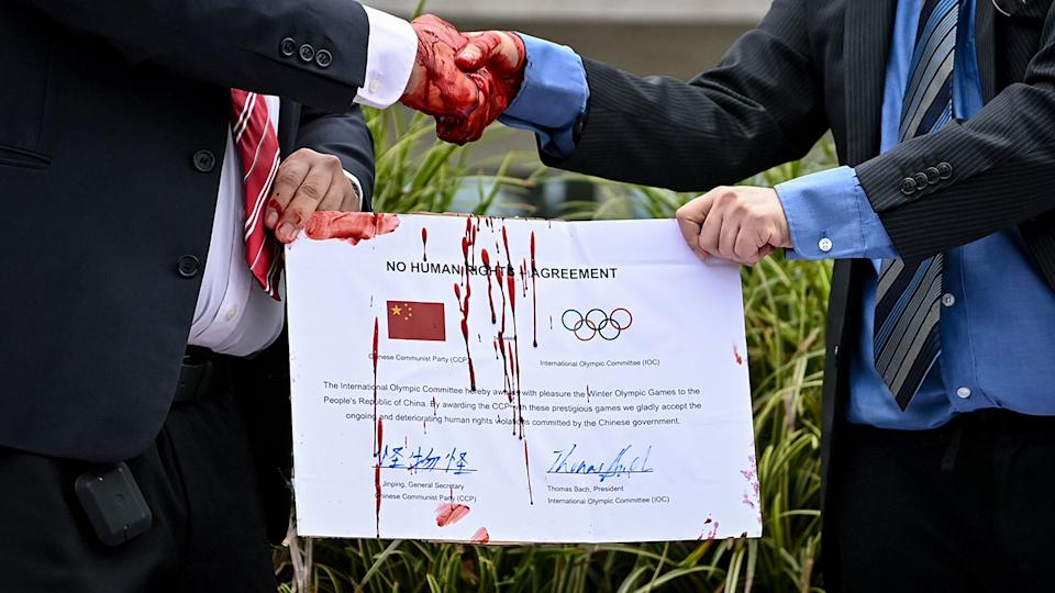 Protesters, pictured here shaking hands in front of the IOC headquarters.