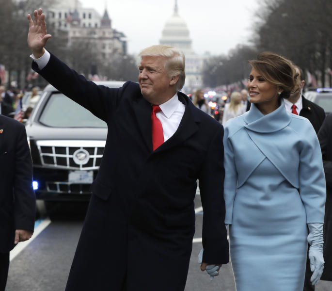 FILE- In this Jan. 20, 2017 file photo, President Donald Trump waves as he walks with first lady Melania Trump during the inauguration parade on Pennsylvania Avenue in Washington. Big money from billionaires, corporations and a roster of NFL owners poured into Donald Trump's inaugural committee in record-shattering amounts, to pull off an event that turned out considerably lower-key than previous inaugural celebrations. (AP Photo/Evan Vucci, Pool, File)