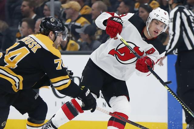 New Jersey Devils' Taylor Hall (9) sends the puck past Boston Bruins' Jake DeBrusk (74) during the first period of an NHL hockey game in Boston, Saturday, Oct. 12, 2019. (AP Photo/Michael Dwyer)