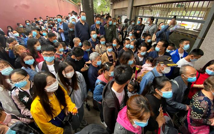 Tourists wearing masks to protect from the coronavirus line up for security checks before visiting the Tiananmen Square area in Beijing - AP