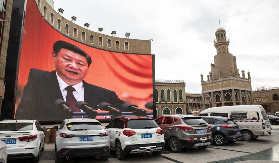 Vehicles stand in a parking lot as a large screen shows an image of Chinese President Xi Jinping in Kashgar, Xinjiang. File photo: Bloomberg