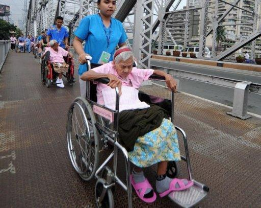 Nurses push wheelchair-bound persons across a bridge while out for a stroll in Manila
