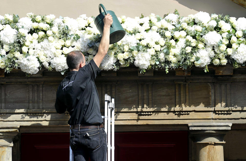 A man waters flowers at Canongate Kirk ahead of the wedding in Edinburgh, Scotland, on July 30, 2011, between Zara Phillips, granddaugter of Britain's Queen Elizabeth II, and England rugby star Mike Tindall. The couple, both world-beating sports stars, tie the knot at Edinburgh's Canongate Kirk in a private ceremony mid-afternoon that has little in common with that of Phillips' cousin, Prince William, when he married the former Kate Middleton three months ago. AFP PHOTO / Andy Buchanan (Photo credit should read Andy Buchanan/AFP via Getty Images)