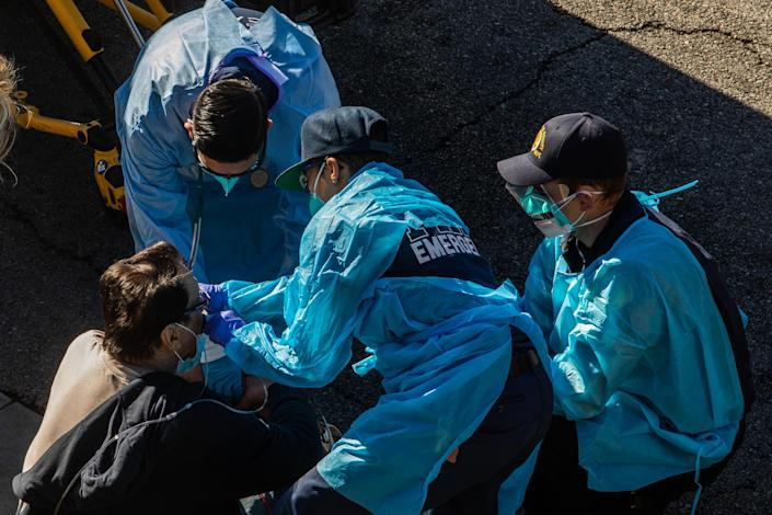Paramedics give oxygen to a potential COVID-19 patient in Los Angeles County on Dec. 29