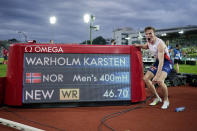 Norway's Karsten Warholm celebrates in front of the scoreboard after running 46.70 seconds to set a new men's 400m hurdles world record at the Diamond League meeting in Oslo, Norway Thursday July 1, 2021. (Fredrik Hagen, NTB via AP)