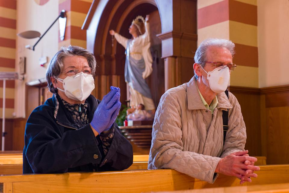 senior couple kneeling in church while wearing masks