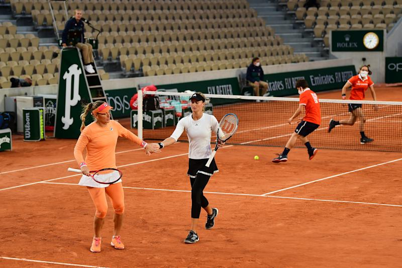 PARIS, FRANCE - OCTOBER 04: Kristina Mladenovic (R) of France and Timea Babos of Hungary celebrate a point in their Women's Doubles third round match against Andreea Mitu and Patricia Tig of Romanie on day eight of the 2020 French Open at Roland Garros on October 04, 2020 in Paris, France. (Photo by Shaun Botterill/Getty Images)