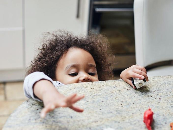 A child reaches for something on a kitchen counter.