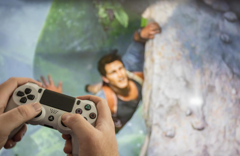 Las Vegas, USA - March 20, 2016: An editorial stock photo showing someone playing the new Uncharted 4 video game on the Playstation 4 (PS4) video game console. The PS4 controller is white with the game being displayed on a large LED tv in the background.